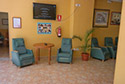 Sala de estar con televisión suspendida en la pared en una residencia de ancianos en Córdoba