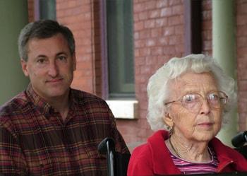 Una anciana ayudada por su hijo