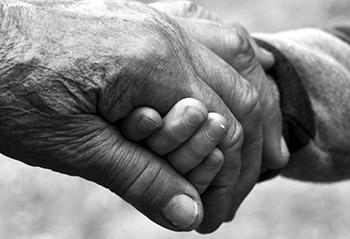 Manos juntas de anciano y persona joven
