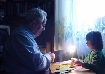 Un hombre mayor juega con su nieta